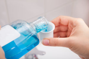 person's hand pouring mouthwash in container